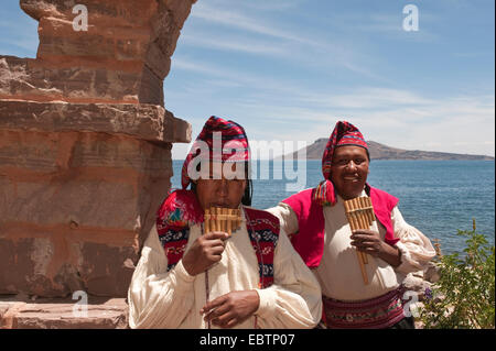 two Indians in traditional clothes playing panflutes at the shore of Lake Titicaca, Peru, Taquile Island, Lake Titicaca - Stock Photo
