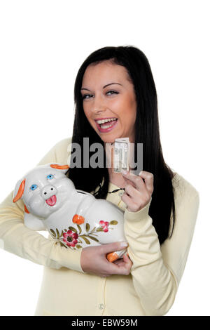young darkhaired woman with piggy bank and banknote - Stock Photo