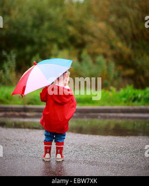 view from behind a little girl with an umbrella - Stock Photo