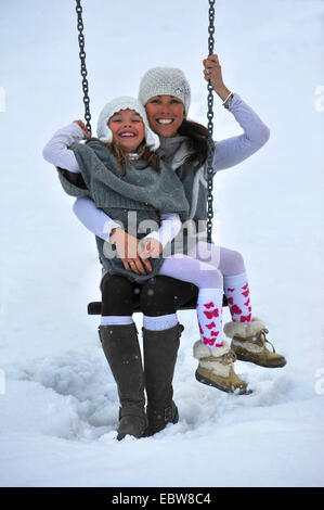 mother and daughter on seesaw in snow - Stock Photo