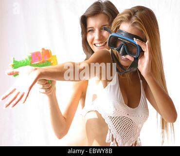 two beautiful young women wearing bikinis fooling around with awater gun and diving goggles - Stock Photo
