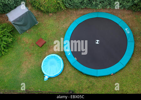 trampoline and paddling pool in garden - Stock Photo