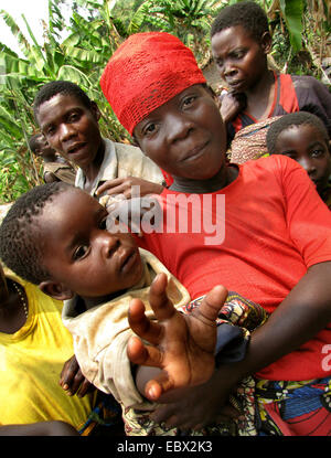 mother with child on her arm in front of other members of the minority of the Batwa living in an isolated rural - Stock Photo