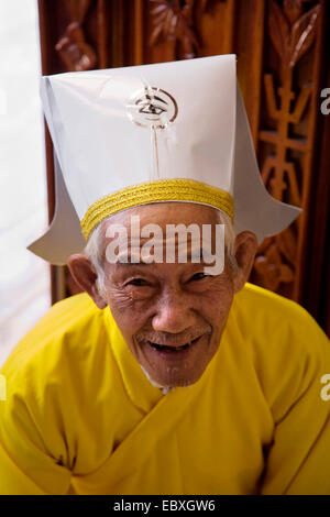 An elderly member of the CAO DAI clergy posing for a portrait inside the CAO DAI GREAT TEMPLE, Vietnam, Tay Ninh - Stock Photo