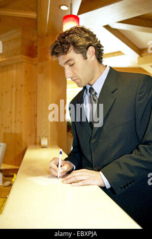 Man checking in, paying at the reception desk - Stock Photo