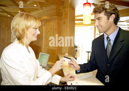 Man checking out, paying at the reception desk - Stock Photo