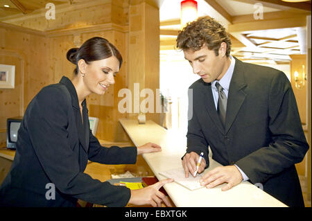 Man checking in at the reception desk - Stock Photo