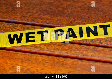 Wet paint sign on a wooden park bench - Stock Photo