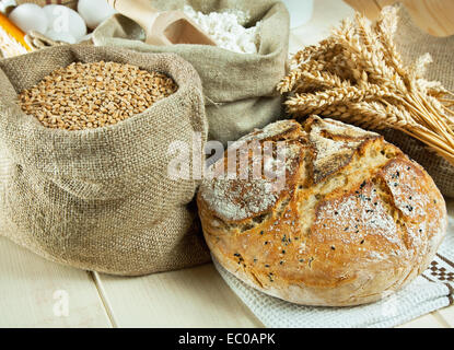 Homemade bread and wheat grain on table - Stock Photo