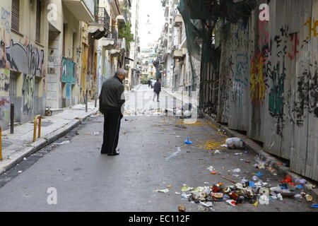 Exarchi, Greece. 7th Dec, 2014. A passersby looks at the burnt rubble in Exarchia. The Clear-up is under way in - Stock Photo