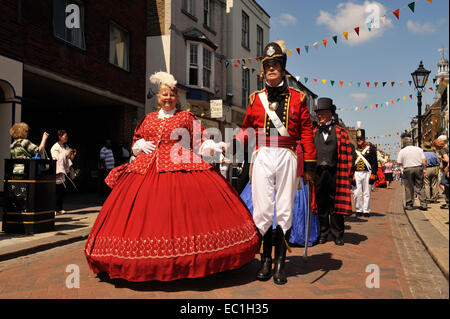 Dickens Festival grand parade, Rochester, Kent. Lady in red dress with officer, Rochester High Street. Novelist - Stock Photo