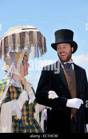 Dickens Festival grand parade, Rochester, Kent. Lady with parasol and gentleman in top hat, on Esplanade beneath - Stock Photo