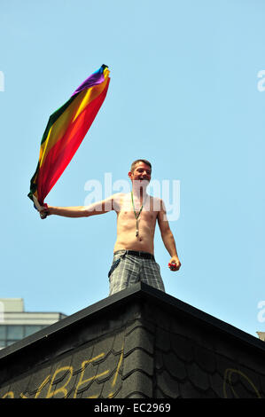 A man waves a rainbow flag on a roof at the 2014 World Pride in Toronto. - Stock Photo