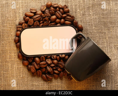 Brown coffee beans with cup and blank label on sack - Stock Photo