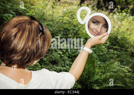 Young brunette is looking to the mirror in outdoors. - Stock Photo