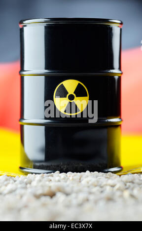 Atomic waste barrel in front of German national colours - Stock Photo