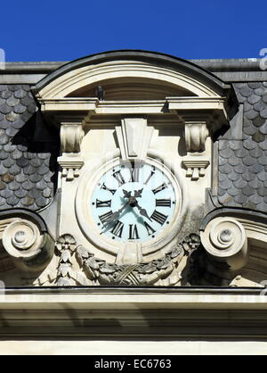 Close up of a clock on old building roof by beautiful day - Stock Photo
