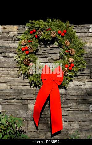 Christmas wreath with pine cones and large red bow hanging on a natural stone wall - Stock Photo