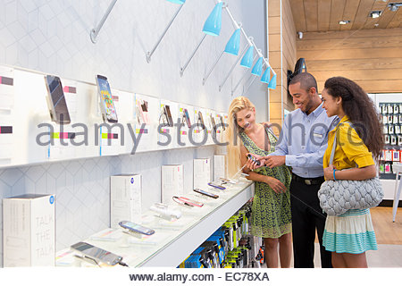 Store manager assisting two female customers in phone store - Stock Photo