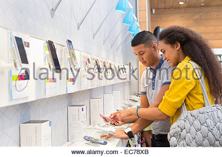 Store assistant helping female customer in phone store - Stock Photo