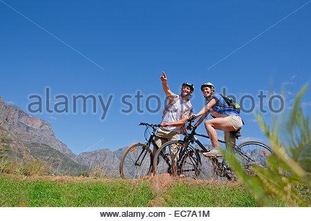 Couple mountain biking in countryside - Stock Photo