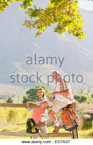 Senior couple out for walk resting on a fence in countryside - Stock Photo