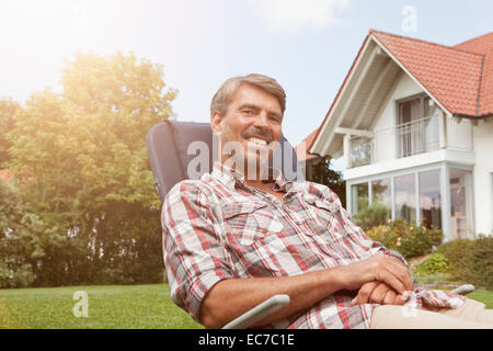 Relaxed man in deck chair in garden - Stock Photo