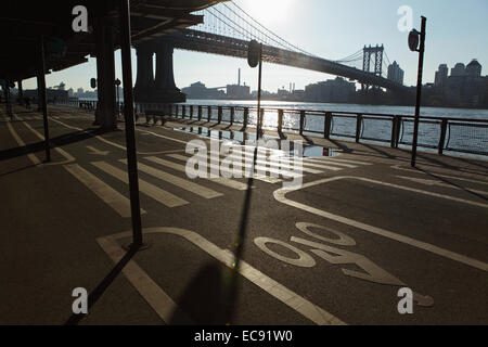 East River Esplanade as the sun rises over the Manhattan Bridge and Brooklyn - Stock Photo