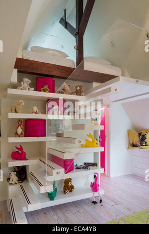 Collection of teddy bears and hares by Ottmar Hörl on open shelving tucked into floating stairs leading to mezzanine - Stock Photo