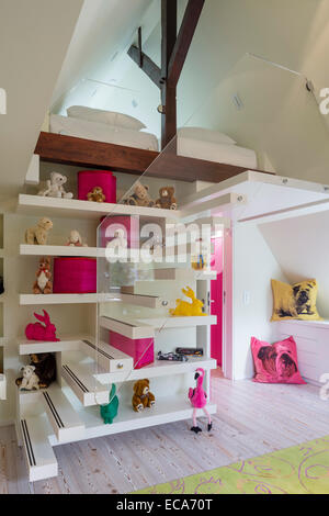 Collection of teddy bears and rabbits on open shelving tucked into floating stairs leading to mezzanine - Stock Photo
