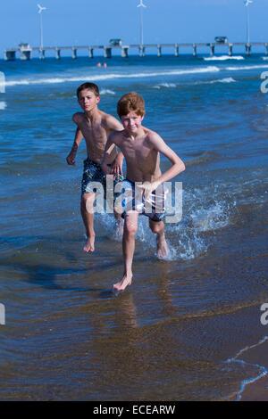 Two boys running along beach - Stock Photo