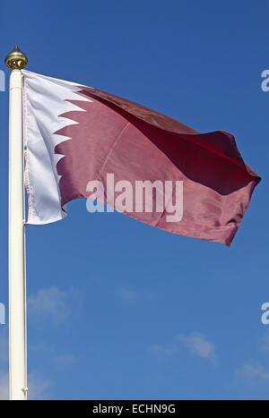 National flag of Qatar on blue sky background - Stock Photo