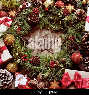 a rustic wooden table full of gifts, and christmas ornaments, such as a natural wreath with branches, berries and - Stock Photo