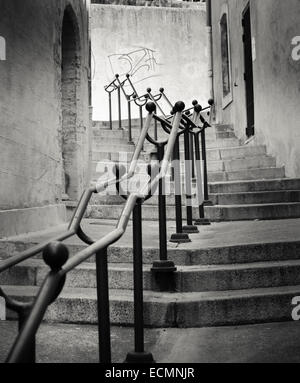 Metal hand rails lead the eye up stone steps to graffiti in the papal town of Avignon, Provence, France - Stock Photo