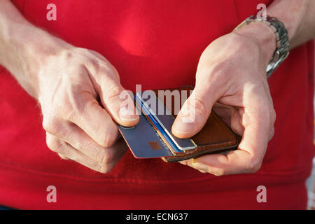 A man in red jumper removing a visa credit card from a wallet to pay for a purchase. England, UK, Britain - Stock Photo