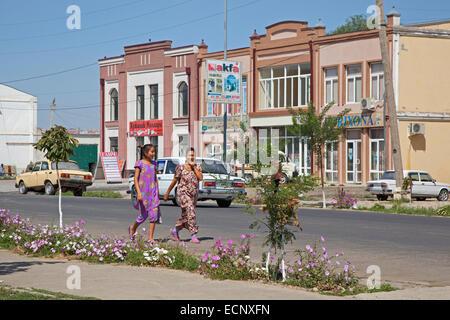 Two Uzbek women walking in street in a village near Samarkand in Uzbekistan - Stock Photo