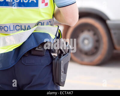 police officer in hi-visibility jacket control traffic, back view - Stock Photo