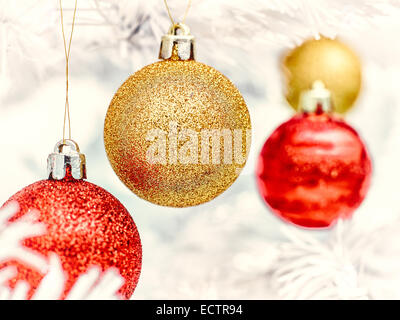 Red and golden balls decorates the white christmas tree - vintage tinted - Stock Photo