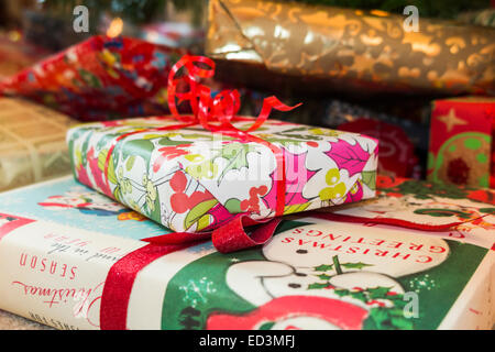 Colourful Xmas presents under a Christmas tree - Stock Photo