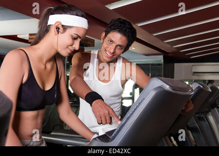 indian sports Trainer and lady tread Mill  Running - Stock Photo