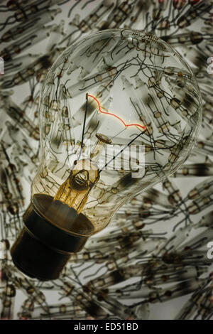 Glowing supported red hot tungsten wire filament in clear light bulb chamber indicating flow of electricity and - Stock Photo