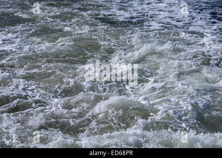 spindrift behind a ship on north sea - Stock Photo