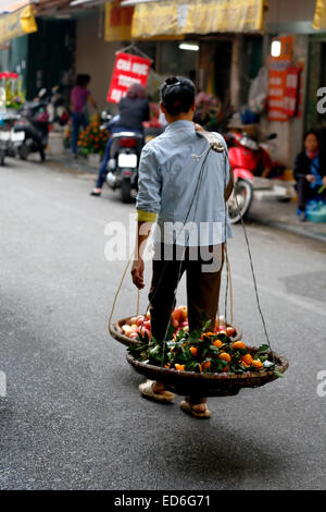 Man carrying fruit on double basket, Old Quarter (aka The 36 Streets), Hanoi, Vietnam - Stock Photo