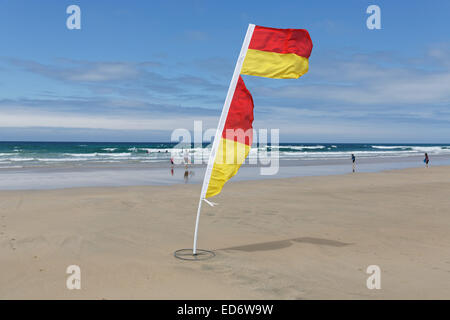 Yellow and red flag of life guards to mark the save part of the fistral beach on a windy day in Newquay, Cornwall, - Stock Photo
