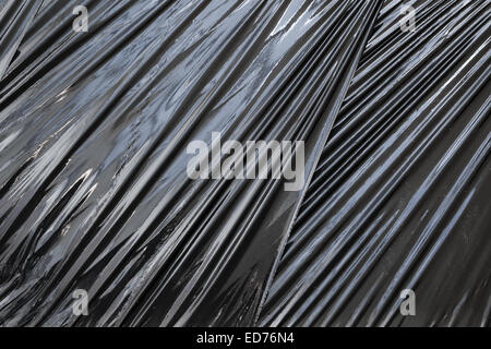 Abstract background photo texture of black polyethylene packing film - Stock Photo