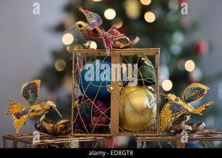 Ornamental Christmas gift boxes with balls and hummingbirds in front of decorated tree - Stock Photo
