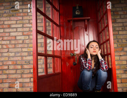 Upset woman sitting blocking her ears in a telephone booth as the handset dangles alongside her ear - Stock Photo