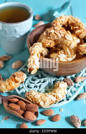 Homemade almond crescent cookies on teal background - Stock Photo
