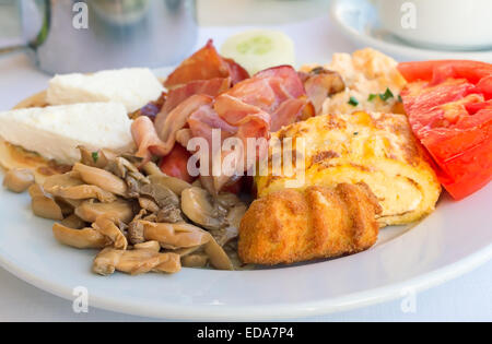 On the tablecloth table on a white plate are ham, scrambled eggs, cheese, mushrooms , tomatoes, varied and tasty - Stock Photo