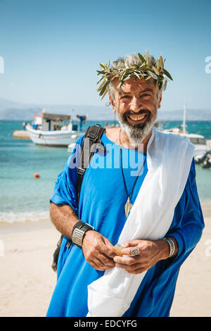 A happy greek man wearing traditional clothing and laurel wreath on a beach in Naxos, Greek Islands - Stock Photo